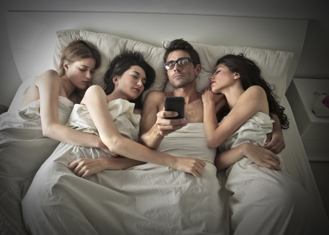 image of guy with three girls together in bed